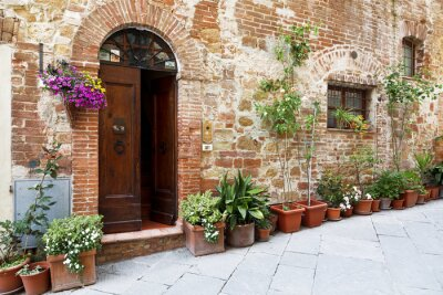 Naklejka The cobbled streets of the beautifully decorated walls with colorful flowers, Tuscany, Italy