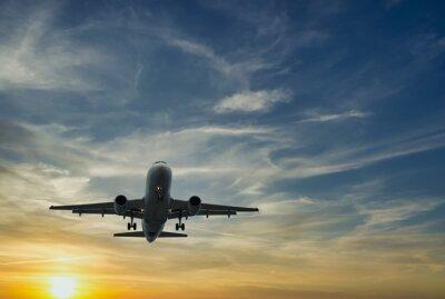 The plane against the blue sunset sky. The setting sun. Sunset
