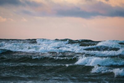 The sea and the waves at sunset. Sky with clouds.