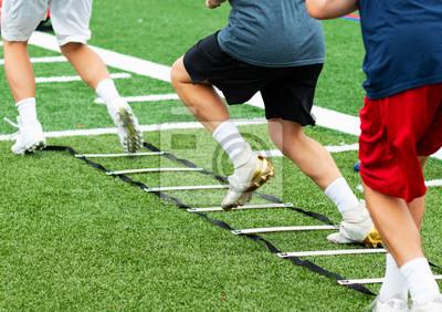 Naklejka Three athletes in cleats doing ladder foot drills on turf field