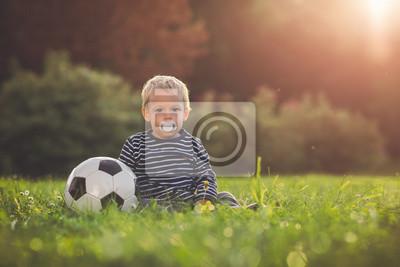 Toddler gry z piłką nożną w zachodzie słońca