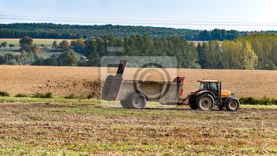 Naklejka tracteur agricole qui fait un épandage de fumier sur le champ