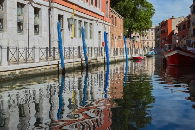 Traditional canal with boats in Venice, Italy. Summer