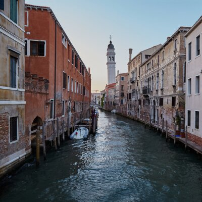 Traditional narrow canal with boats in Venice, Italy. Summer