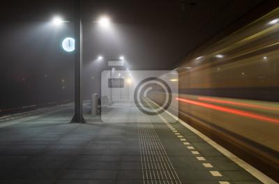 Naklejka Train passing an empty platform at a railroad station during a foggy evening. Groningen, Holland.