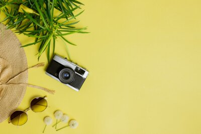 Naklejka Travel concept with green leaves, camera, sun glasses and hat over the yellow background.