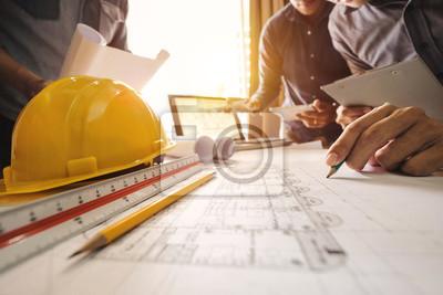 Naklejka Trzech kolegów omawianie danych pracy i tabletu, laptopa z na sprawie projektu architektonicznego w budowie na biurko w biurze