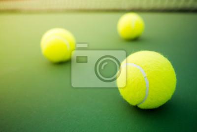 Trzy kule tenisowe na zielony i czerwony twardy sąd