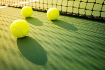 Trzy kule tenisowe na zielony i czerwony twardy sąd z cieniem z sieci
