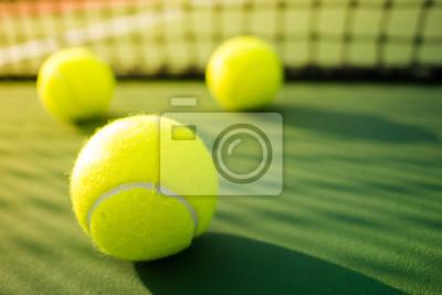 Trzy kule tenisowe na zielony twardy sąd z cieniem z sieci