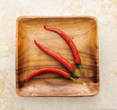Naklejka trzy słodkie red hot chili na tle drewna