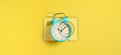 Naklejka Turquoise vintage alarm clock on yellow background. Top view. Flat lay