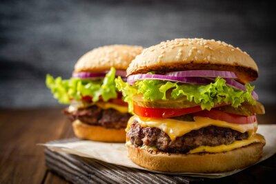 Naklejka Two homemade tasty burgers on wood table. Selective focus.
