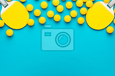 Naklejka two rackets and many balls for table tennis on turquoise blue background. flat lay image of many table tennis balls and paddles. minimalist photo of yellow ping-pong equipment with copy space