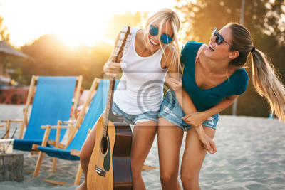 Naklejka Two young female friends hangout at the beach ,singing and relaxing in beautiful summer sunset.They hug each other.