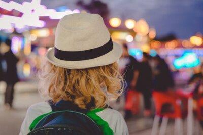 Naklejka Tylny widok radosna śliczna dziecko chłopiec na nocy bokeh amuzement parku outdoors tle