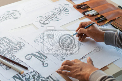 Naklejka Typography Calligraphy artist designer drawing sketch writes letting spelled pen brush ink paper table artwork.Workplace design studio.