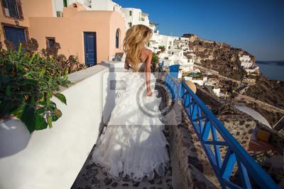 Uciekająca panna młoda w sukni ślubnej w Santorini w Grecji