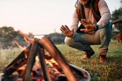 Naklejka Unrecognizable man warms hands over campfire while camping in nature.