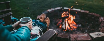 Naklejka Unrecognizable Woman Enjoying Hot Tea From A Tin Cup In Campsite With Fire Pit. Girl In Folk Blanket By Burning Campfire with mountain landscape with evening sunset sky over the forest and hills.