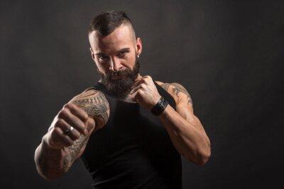 Naklejka Uomo moro muscoloso, tatuato con la barba, stai un posizione di combattimento pronto all'attacco , isolato su sfondo nero