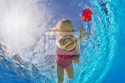 Uśmiechnięta dziewczyna w basenie pod wodą basen na tropikalnej czerwonym kwiatem