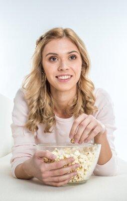 Uśmiechnięta kobieta jedzenia popcorn