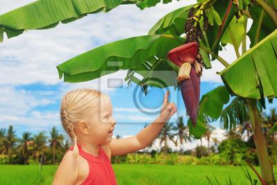 Uśmiechnięte dziecko odkrywania natury - kwiat bananów i owoców