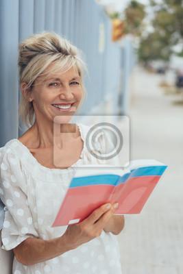 Naklejka Uśmiechnięty starszy obywatel stoi w mieście trzyma w ręku przewodnika