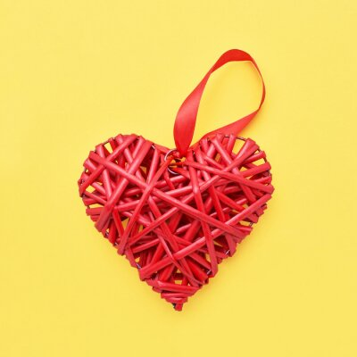 Valentines Day background. Red wicker heart on yellow background. Copy space, top view. Valentines Day concept