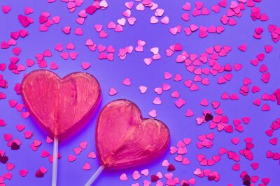 Valentines Day background. Two candy hearts with glitter on purple backdrop. Top view, copy space