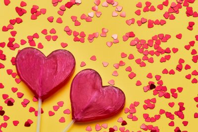 Valentines Day background. Two candy hearts with glitter on yellow backdrop. Top view, copy space