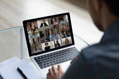 Naklejka View over businessman shoulder group video call on laptop screen, diverse colleagues business partners chatting online, engaged in internet conference, meeting by webcam, distance work concept