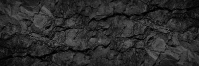 Naklejka Volumetric rock texture with cracks. Black stone background with copy space for design. Wide banner.
