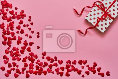Walentynki tło. Czerwone serca i pudełko na różowym tle. Skopiuj miejsce, widok z góry