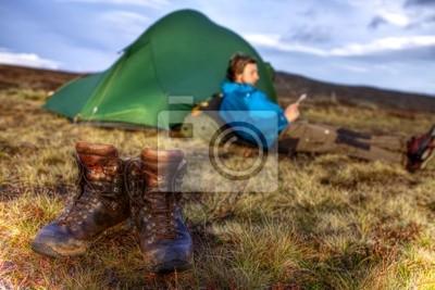 Wanderschuhe mit Zelt und Wanderer im Hintergrund