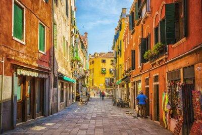 Naklejka Wąski kanał wśród starych kolorowych domów w Wenecji z cegły