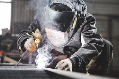 Naklejka Welder working with welding on metal frames in an industrial plant.