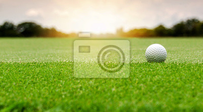 Naklejka White Golf ball on green course to be shot on blurred beautiful landscape of golf course in bright day time with copy space. Sport, Recreation, Relax in holiday concept