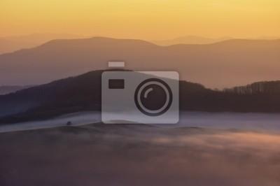 widok na wzgórza na kolorowe jesienią mglisty poranek