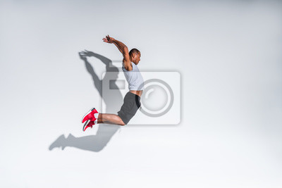 Naklejka widok z boku młodego sportowca african american skoków na szaro