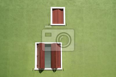 Windows z brązowym migawki na jasnozielonej ścianie. Włochy, Wenecja, wyspa Burano. Minimalizm