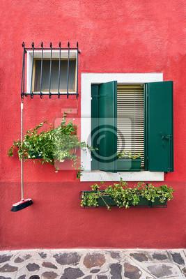 Windows z zielonymi żaluzjami i kwiatami na sławnej wyspie Burano, Wenecja, Włochy