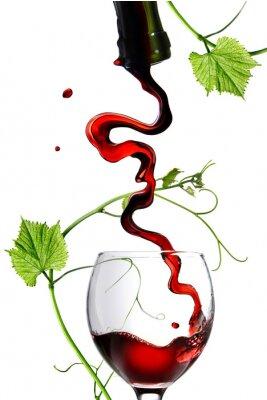 Naklejka Wlewanie wina czerwonego w szkle z prętem na białym tle