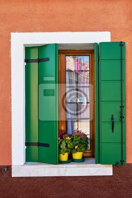 Włochy, Wenecja, wyspa Burano. Tradycyjne kolorowe ściany i okna z jasnymi zielonymi okiennicami i kwiatami w doniczce.