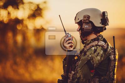 Naklejka wojskowy żołnierz z bronią o zachodzie słońca. strzał, trzymając broń, kolorowe niebo. pojęcie wojskowe.