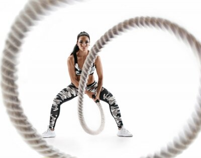 Naklejka Woman doing exercises with battle rope. Photo of muscular model in military sportswear isolated on white background. Strength and motivation
