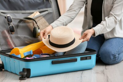 Naklejka Woman packing suitcase at home