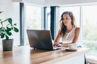Naklejka Woman using laptop while sitting at home