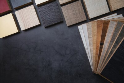 wood texture laminate furniture and flooring material samples on dark stone background with copy space